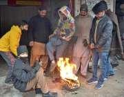 فیصل آباد: شہر میں ٹھنڈے موسم کے دوران گرم رہنے کے لئے آگ کے آس پاس کھڑے ..