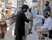 راولپنڈی:موتی بازار میں دکاندارآنے والے گاہکوں کو سینی ٹائزر سے ہاتھ ..