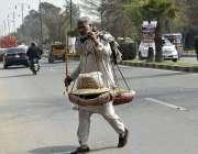 فیصل آباد:ایک محنت کش بھنے ہوئے دانے بیچ رہا ہے