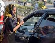 لاہور، ایک محنت کش بچی سگنل پر گاڑی کے شیشے صاف کر رہی ہے۔