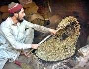 پشاور: ایک مزدور اپنے کام کی جگہ پر مونگ پھلی بھون رہا ہے۔