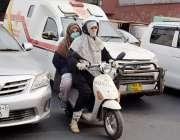 لاہور، دو خواتین سکوٹی پر اپنی منزل کی جانب گامزن ہیں۔