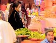 کراچی، کورونا کی دوسری لہر سے بچائو کی خاطر خریداری کیلئے آئی ایک خاتونن ..