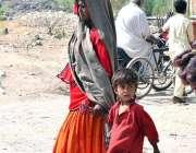 حیدرآباد: ایک خانہ بدوش خاتون اپنے بچے کے ساتھ  پینے کا صاف پانی بھرنے ..