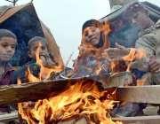 کراچی: کورنگی میں گھر کے باہر خود کو گرم رکھنے کے لئے ایک خاتون اپنے ..