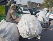 لاہور:ایک محنت کش ہتھ ریڑھی پر بھاری بورے رکھ کر لے جارہا ہے۔