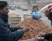 لاہور:مال روڈ کے قریب ایک شہری ریڑھی والے سے مونگ پھلی خرید رہا ہے.