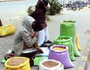 کراچی: سڑک کے کنار صارفین کو راغب کرنے کے لئے ایک فروش دانہ بیچ رہا ہے۔