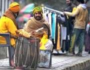 راولپنڈی: ٹھنڈے موسم میں اپنے آپ کو گرم رکھنے کے لئے روایتی ڈھولچی شمس ..
