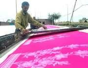 لاہور: ایک مزدور اپنے کام کی جگہ پر کپڑوں کے ٹکڑوں پر چھاپنے میں مصروف۔