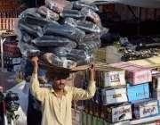لاہور:ایک محنت کش سر پر وزن اٹھائے جارہا ہے۔