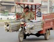 لاہور، ایک ڈرائیور چنگ چی پر لوہے کے راڈ رکھے جا رہا ہے جو کسی بھی ناشگوار ..