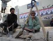 کراچی: مزدور سڑک کے کنارے بیٹھ کر اپنی روز مرہ نوکری کے منتظر ہیں۔