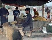 لاہور: ایک دکاندار اپنے کام کی جگہ پر چنے بھون رہا ہے۔