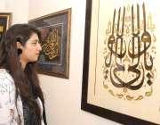 لاہور : ایک لڑکی الحمرا میں منعقدہ خطاطی کی نمائش دیکھ رہی ہے۔