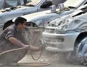 اسلام آباد: ایک پینٹر اپنی ورکشاپ میں گاڑی پینٹ کر رہا ہے۔