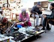 لاہور : ایک خاتون سڑک کنارے لگائے گئے سٹال سے چشمه خرید رہی ہے۔