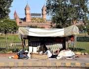 لاہور ریلوے اسٹیشن کے سامنے فٹ پاتھ پربنائی جھگی میں ایک شخص آرام کر ..