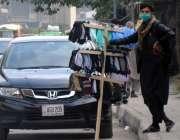 راولپنڈی، محنت کش مری روڈ کے کنارے ماسک اور گلوز فروخت کر رہا ہے۔