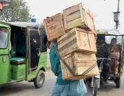 لاہور : منڈی میں محنت مزدوری کرنے والا ایک محنت کش اپنی کمر پرفروٹ کے ..