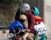 راولپنڈی، موٹرسائیکل سوار فیملی ماسک پہنے مری روڈ سے گزر رہی ہے۔