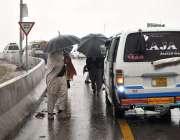 اسلام آباد: بارش سے بچانے کے لئے چھتریوں کی آڑ میں اسٹاپ پر کھڑے مسافر۔