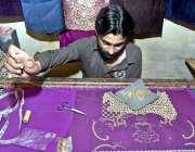 لاڑکانہ: پرانا ریشمگلی میں اپنے کارکن کپڑے کے ٹکڑے پر کڑھائی کے کام ..