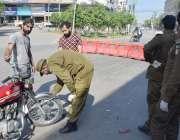 لاہور، پولیس اہلکار دفعہ 144 کی خلاف ورزی کرنے پر نوجوانوں کی موٹرسائیکل ..
