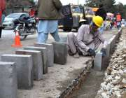 کوئٹہ: ایک مزدور سڑک کے کنارے سیمنٹ والے بلاکس کو ٹھیک کرنے میں مصروف ..