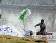 ملتان: مقامی نہر پر مزدور خالی بیگ دھونے کے بعد نہر سے باہر پھینک رہے ..