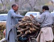 اسلام آباد: سڑک کے کنارے گرین بیلٹ سے جمع ہونے کے بعد دو افراد خشک درخت ..