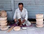 لاہور : ایک دکاندار ہاتھ سے لکڑی کی ٹوکری بنانے میں مصروف ہے۔