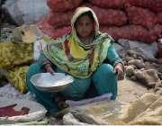 لاہور: سبزی منڈی میں ایک محنت کش خاتون لہسن فروخت کر رہی  ہے۔