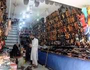 راولپنڈی: لاک ڈاون میں نرمی کے بعد شہری ایک دکان سے جوتے پسند کر رہے ..