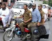لاہور : موٹرسائیکل پر سوار تین پولیس اہلکار ہیلمٹ اور کورونا ایس  اوپیز ..