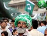 کراچی: پیپر مارکیٹ میں ایک معمر شہری نے جشن آزادی کے حوالے سے وگ پہن ..