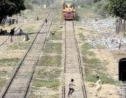 کراچی، کالا پل ریلوے لائن پر چلتی ٹرین کے سامنے سے شہری گزر رہے ہیں ..