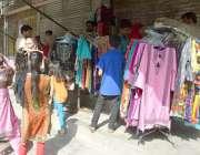 لاہور:شہری اسلام پورہ میں بند دکانوں کے سامنے لگائے گئے سٹال سے ریڈی ..