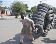 لاہور، کورونا وائرس کے باعث لاک ڈائون میں ایک محنت کش ہتھ ریڑھی پر ٹائر ..
