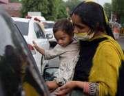 لاہور: ایک خاتون اپنی بیٹی کے ہمراہ سگنل پر بھیک مانگ رہی ہے۔