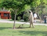 لاہور: پی ایچ اے کا ملازم گریٹر اقبال پارک میں مشین کے ذریعے گھاس کاٹ ..