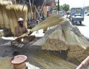 فیصل آباد: ایک شخص اپنے سڑک کنارے کام کرنے کی جگہ پر جھاڑو بنا رہا ہے۔