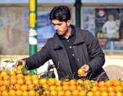 اسلام آباد: ایک دکاندار اپنے سڑک کنارے سنترے بیچنے کے لیے ترتیب سے لگا ..