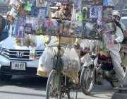 فیصل آباد: ایک دکاندار اپنے سائیکل پر گاہکوں کی تلاش میں جارہا ہے۔