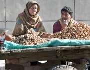 لاہور: ایک محنت کش خاتون مونگ پھلی اور اخروٹ فروخت کررہی ہے۔