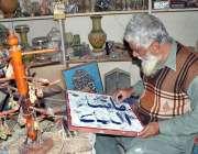 ملتان: ایک فنکار کرافٹ بازار میں فریم ورک میں مصروف ہے۔