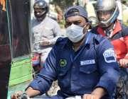 لاہور : موٹرسائیکل سوار شہری کرونا وائرس سے بچاؤ کیلئے فیس ماسک پہنے ..