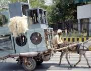 لاہور : ایک محنت کش ائیر کولر گدھا ریڑھی پررکھ  لر مارکیٹ جارہا ہے، گرمی ..
