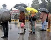 راولپنڈی: بس سٹاپ پر کھڑے شہری چھتری تانے گاڑی کا انتظار کررہے ہیں۔