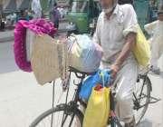 لاہور : ایک بزرگ سائیکل پر ہاتھ سے جھلنے والے پنکھے فروخت کرنے کیلئے ..
